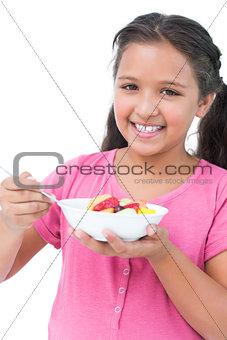 Little girl eating fruit salad