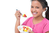 Smiling little girl eating fruit salad