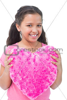 Little girl holding cushion in the shape of a heart