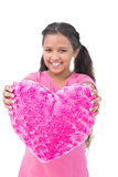 Little girl showing cushion in the shape of a heart