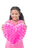 Smiling little girl showing cushion in the shape of a heart
