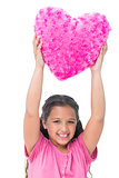 Smiling little girl holding cushion in the shape of a heart