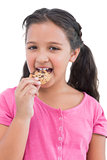 Smiling little girl eating a cookie