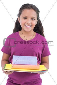 Little girl holding notebooks and books for her homework
