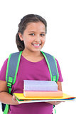 Smiling little girl wearing book bag and holding her homework