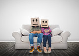 Couple sitting on couch with cardboard boxes over their head