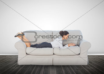 Attractive businesswoman lying on a couch