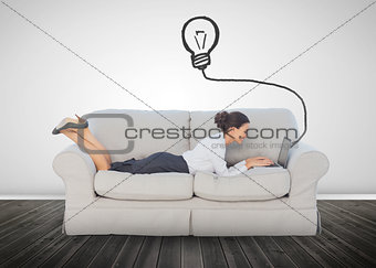 Attractive businesswoman lying on a couch and typing on her laptop