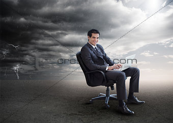 Attractive businessman using his laptop outside during stormy weather