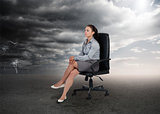 Businesswoman sitting in middle of opposite weather settings