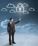 Businessman holding a floating padlock around clouds