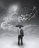 Businessman under an umbrella looking at drawings