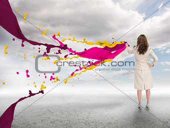 Creative businesswoman with paints splash