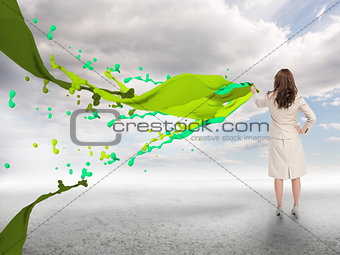 Creative businesswoman with green paint splash