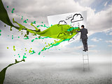 Businessman standing on a ladder with paint splash