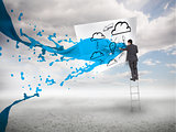 Businessman standing on a ladder with blue paint splash