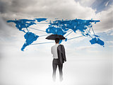 Businessman with an umbrella looking at a world map