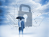 Businessman under an umbrella looking at a big padlock