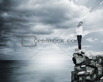 Thoughtful businessman standing at the edge of a cliff