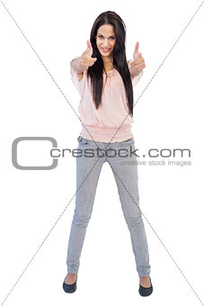 Smiling brunette does thumbs up at camera