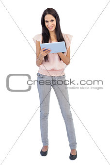 Smiling brunette using tablet pc
