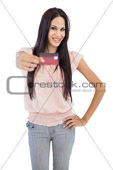 Smiling brunette showing her credit card to camera