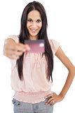 Happy brunette showing her credit card to camera