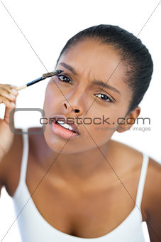 Beautiful woman putting mascara on her eyelash