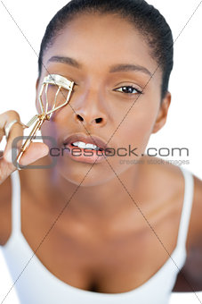 Concentrated woman using curler for her eyelash