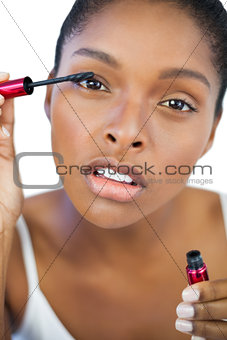 Concentrated woman using mascara for her eyelashes