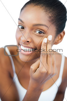 Smiling woman putting moisturizer on her face