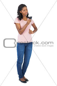 Young woman looking at her mobile phone with hand on hip