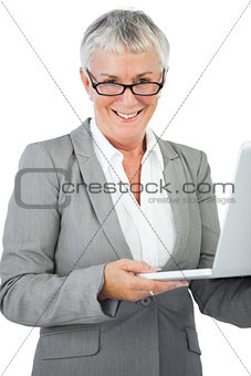 Smiling businesswoman with glasses holding her laptop