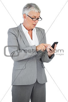 Businesswoman with glasses texting a message on her mobile phone