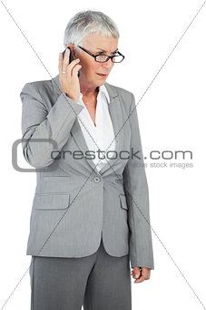 Unsmiling businesswoman calling someone with her mobile phone