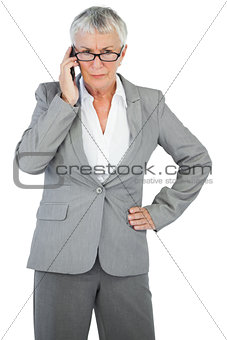 Furious businesswoman calling someone with her hand on hip