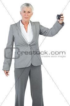Unsmiling woman holding camera for taking picture
