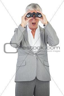 Astonished businesswoman looking at something through binoculars