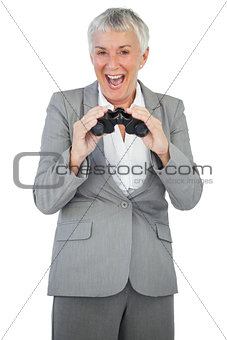 Smiling businesswoman holding binoculars