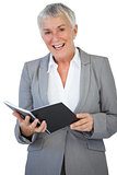 Cheerful businesswoman holding notepad