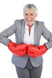 Cheerful businesswoman wearing boxing gloves