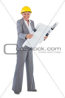 Smiling architect wearing hardhat and holding plan