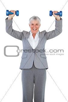 Smiling businesswoman holding dumbbells