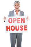 Surprised estate agent holding sign for open house