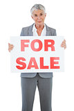 Estate agent holding for sale sign