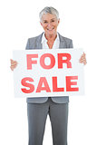 Smiling estate agent holding for sale sign