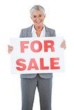 Smiling estate agent holding for sale sign