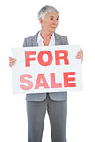 Estate agent holding sign for sale and looking away