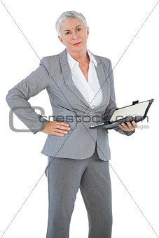 Businesswoman holding diary with her hand on hip