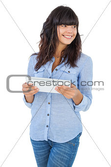Cute woman holding tablet pc and looking away